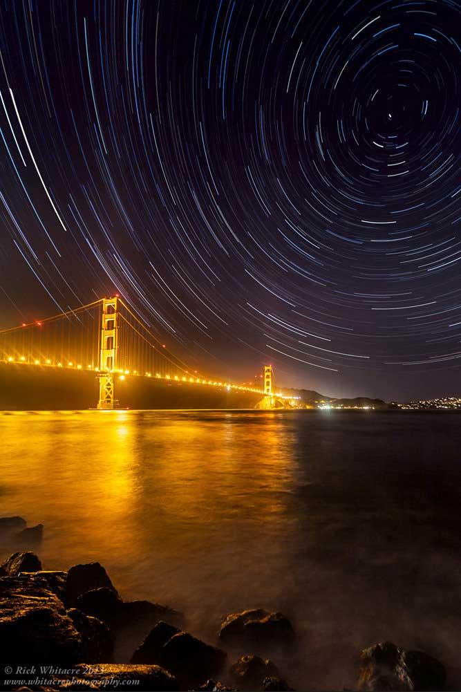 Rastro das estrelas acima da Ponte Golden Gate, na Califórnia. Apesar do brilho intenso da ponte, a câmera pôde captar algumas das estrelas mais brilhantes. Nossos olhos não têm a mesma sorte, devido à poluição luminosa das cidades.